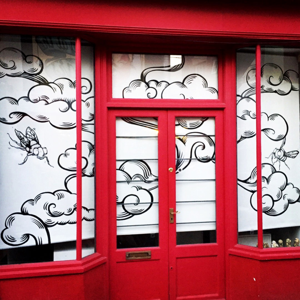 Clouds and flies painted on the shop blinds for the Lucas Antics studio