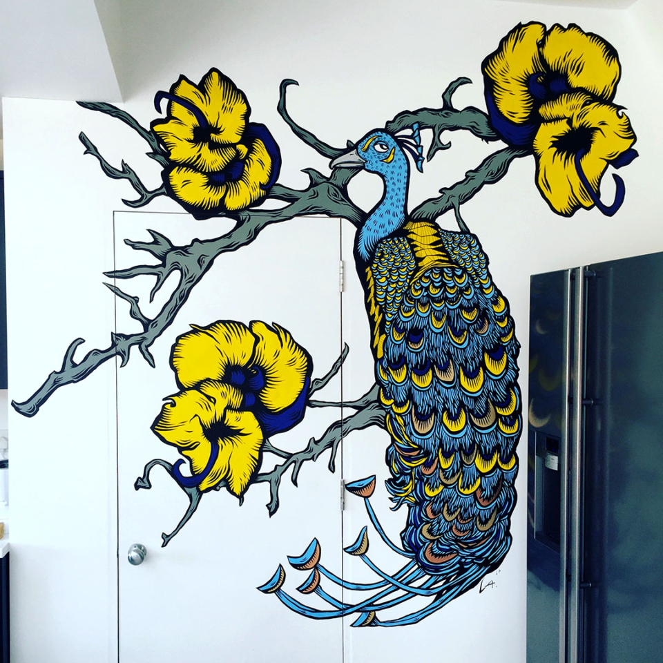Bright coloured peacock painted to match the kitchen tiles