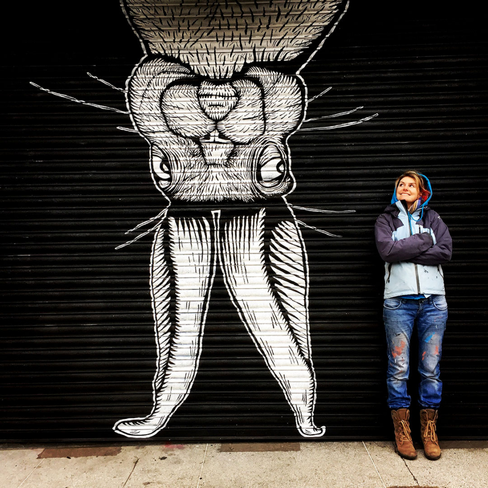 Alex Lucas standing in front of giant upside down rabbit mural